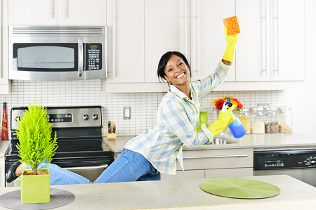 Woman wearing yellow rubber gloves in the kitchen holding a sponge and cleaning spray bottle