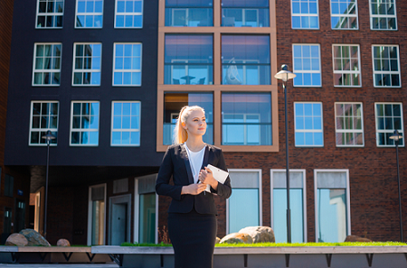 business woman standing outside building holding notebook